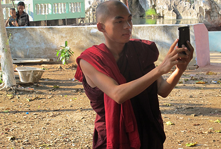 A young monk and smart phone. Photo by Belinda Cranston.