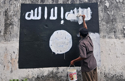 INDONESIA, Surakarta City: A government worker removes ISIS (Islamic State of Iraq and Syria) flags painted on to walls near Veteran Street in Surakarta City in an attempt to discourage the promotion of the jihadist group in the region. (AAP Image/NEWZULU/AGOES RUDIANTO). NO ARCHIVING, CROWD SOURCED CONTENT, EDITORIAL USE ONLY