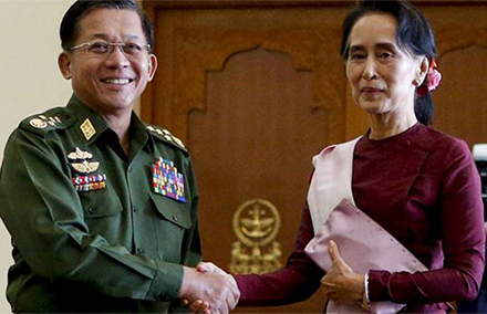 Min Aung Hlaing shakes hands with Aung San Suu Kyi.