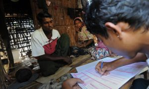 A Muslim man (left) answers questions during a census taking in the village of Barasa. Photo by AFP.