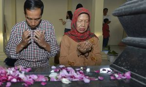 Indonesian presidential candidate Joko Widodo and his mother pray at his father's tomb. Photo by AFP.