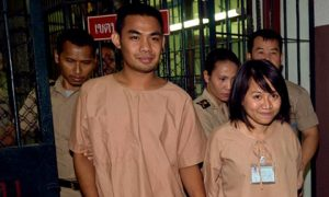 Thai student Patiwat Saraiyaem, 23, left, and activist Porntip Mankong, 26, are escorted by prison security guards after their verdict at the Criminal Court in Bangkok. Photo: AFP.