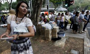 A volunteer helps Myanmar citizens in Singapore cast their advanced vote. Photo: Reuters