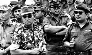 General Suharto (second from left) and other army officers attend the funeral of their slain comrades in 1965.