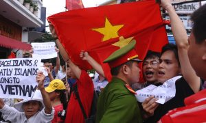 Protesters shout anti-Chinese slogans next to a policeman during a march in downtown Hanoi on June 26, 2011. The protesters rallied in the Vietnamese capital for the fourth weekend in a row to protest against a territorial dispute over a group of islands in the South China Sea. AFP PHOTO/HOANG DINH Nam (Photo credit should read HOANG DINH NAM/AFP/Getty Images)