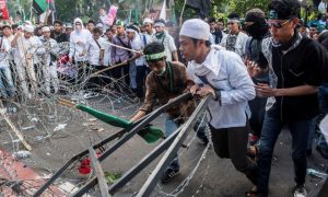 Muslim students brokes the barb wire during a protest against Jakarta's incumbent governor Basuki Tjahaja Purnama, an ethnic Chinese Christian running in the upcoming election, in Jakarta, Indonesia, November 4, 2016  in this picture taken by Antara Foto. Antara Foto/M Agung Rajasa/via REUTERS